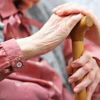 Assisting an elderly woman with a walking stick